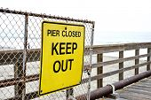 Bright Yellow Sign At A Beach Pier That Reads Pier Closed Keep Out poster