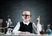 Clever Little Girl Scientist In Glasses At Desk In Laboratory Class. Research And Education In Schoo poster