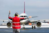 Aviation Marshall / Supervisor Meets Passenger Airplane At The Airport. Ground Crew In The Signal Ve poster