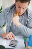 foto of midterm  - Student using a calculator while doing his homework - JPG