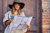 Happy  woman on vacation sightseeing city with map poster