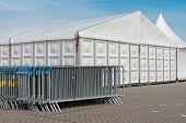 pic of marquee  - Crush barriers near a big marquee and a blue sky - JPG
