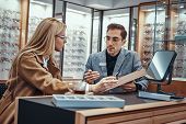 Woman Is Choosing Eyeglasses While Male Optician Sitting Near With Another Eyeglasses. poster