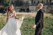 Gorgeous Bride And Groom Having Fun And Dancing In Evening Sunlight Near Old Castle In Park. Stylish poster