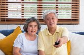 Asian Couple Senior Sitting On Sofa And Use Remote Control To Change Channel And Watching Tv In Livi poster