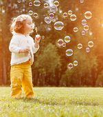 Little child blows bubbles in the sunset poster