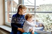 Happy Adorable Kid Boy And Cute Baby Girl Sitting Near Window And Looking Outside On Snow On Christm poster