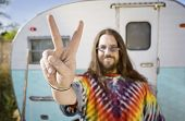 foto of peace-sign  - Friendly Hippie with Long Hair in Front of His Trailer making a peace Sign - JPG