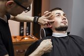 Beard Haircut In A Barbershop, A Young Guy Shaving His Beard With A Razor, Close-up poster
