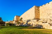 Adorable green lawn growing under ancient walls. Hot summer sunset. The fortress wall of old Jerusal poster