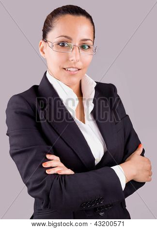 Portrait of a happy young business woman standing with folded hand against grey background
