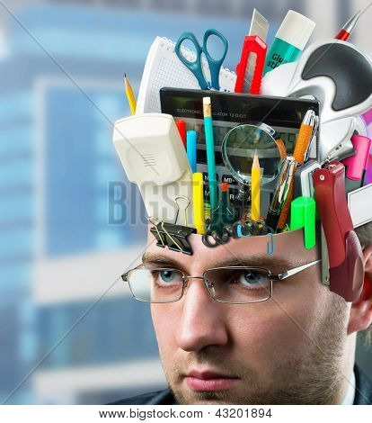 Confident businessman with office accessories in head