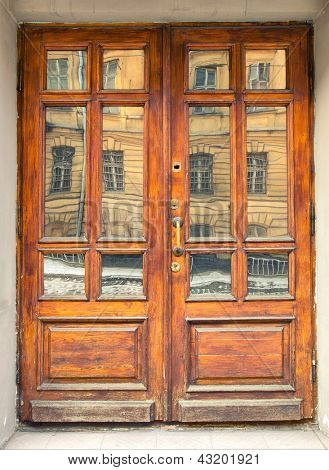 Old weathered wooden door with distorted reflection