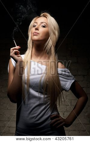 Portrait Of Young Blonde Woman With A Cigarette