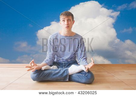 Teenager Making Funny Face While Sitting In Lotus Pose