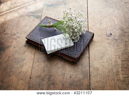 Vintage book and a small bouquet of baby's breath flowers and a blank sheet of folded white memo paper, on a well used old desk or wooden surface.