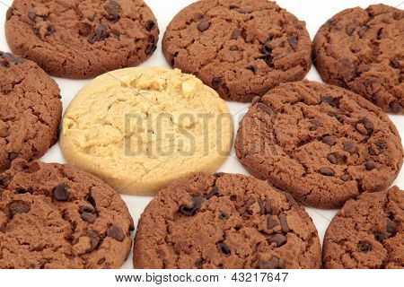 Chocolate chip cookies with one light chocolate cookie over white background. Selective focus.