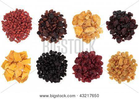 Goji berry, sultana, pineapple, cranberry, mango, elderberry, cherry and golden raisin dried fruit over white background.