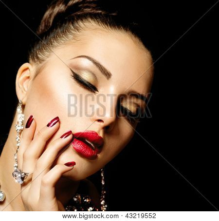 Beauty Woman with Perfect Makeup. Beautiful Professional Holiday Make-up. Red Lips and Nails. Beauty Girl's Face isolated on Black background