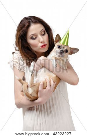 Pretty woman kisses a straw-colored small dog in cap, isolated on white