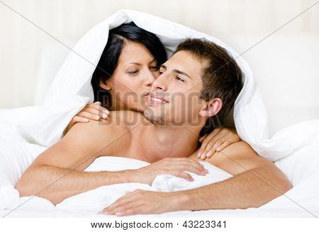 Close up of couple playing in bedroom. Covered with blanket woman lying on the back of the man kisses him