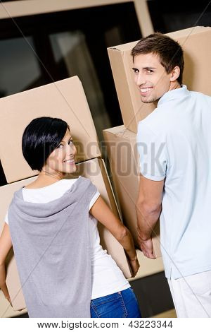 Back view of happy couple carrying cardboard boxes while moving to new house
