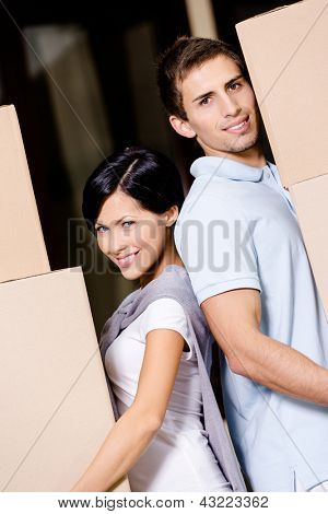 Happy couple stands back to back while carrying cardboard containers and moving to new house