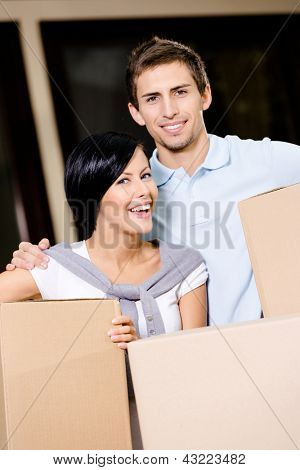 Happy couple carrying cardboard boxes while moving to new house