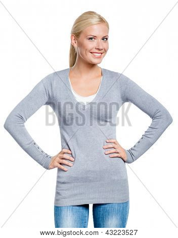 Girl wearing grey sweater stands with hands on the hips, isolated on white