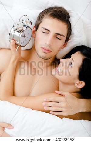 Close up of couple lying in bedroom. Woman holds alarm clock near the ear of man, top view