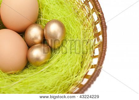 Brown and golden easter eggs are in wattled basket with sisal fibre, isolated on white