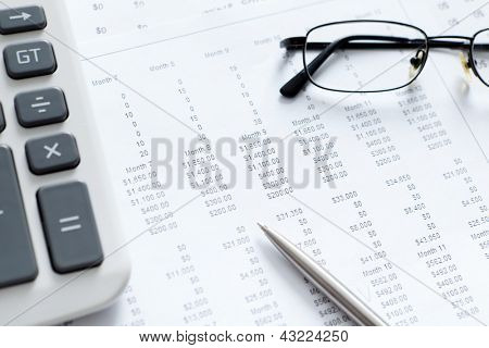 Close up view of business documents, calculator, pen, diagrams and spectacles