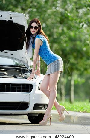 Woman repairing the broken car on the highway. Girl stands near opened hood of the car after an accident