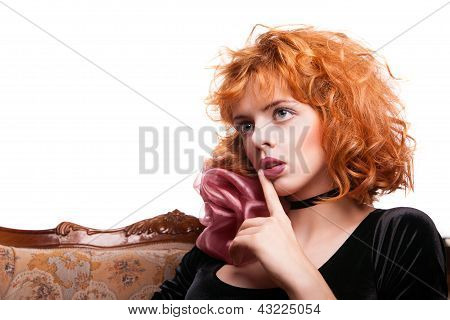 Girl with red hair making a hush gesture