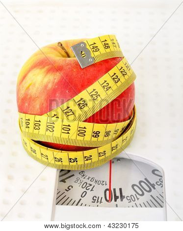 Measuring tape and apple on scales
