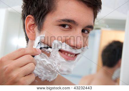 joven afeitado con maquinilla de afeitar y afeitar crema en el baño