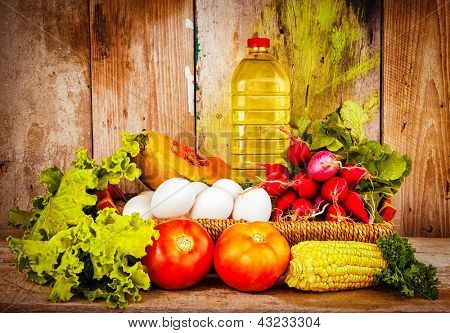 Fresh and colorful vegetables, eggs and a bottle of oil on a basket with a vintage wooden background useful to illustrate healthy or vegetarian food
