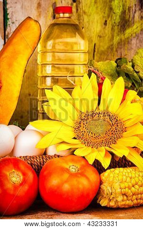 Fresh  vegetables, eggs, flowers and a bottle of oil on a basket with a vintage wooden background useful to illustrate healthy or vegetarian food