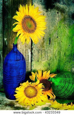 Beautiful vintage image of sunflowers and pottery vases with a grunge wooden planks background