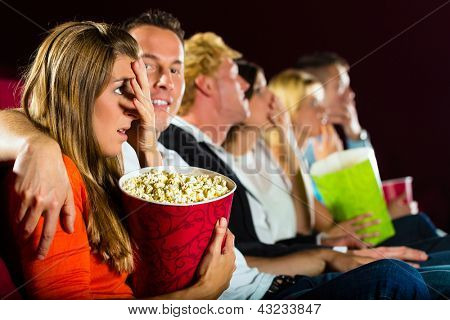 Group of young people watching creepy movie at movie theater