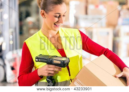 Female worker with protective vest and scanner, scans bar-code of package, standing at warehouse of freight forwarding company