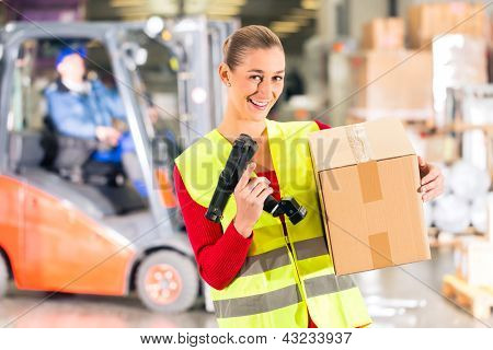 Female worker with protective vest and scanner, holds package, standing at warehouse of freight forwarding company, smiling