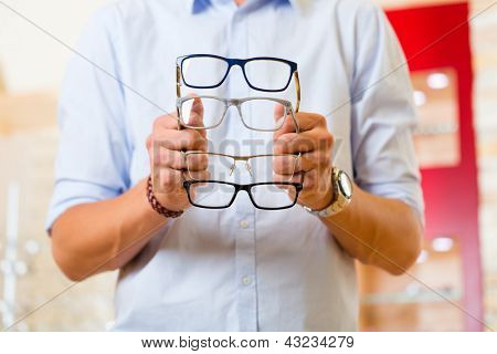Young man at optician with glasses, he might be customer or salesperson