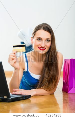Young Woman buying on the Internet online using the laptop, she is paying with her golden Credit Card