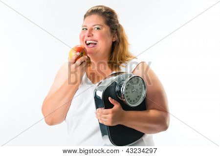 Diet and weight, obese young woman with scale under her arm and apple