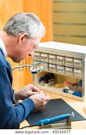 hearing aid acoustician at work, he is working on a hearing aid for hearing impaired persons