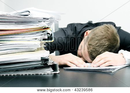 Tired Office Worker And A Pile Of Documents