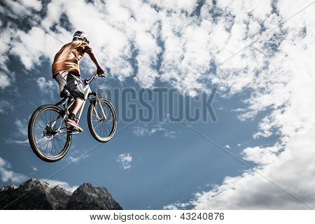 young boy jumps high with his bike