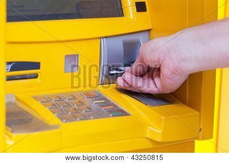 man inserts a plastic card into the ATM
