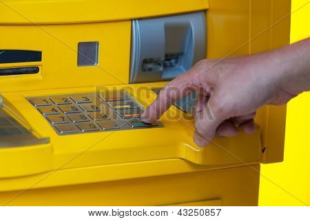 man enters a PIN code in the ATM